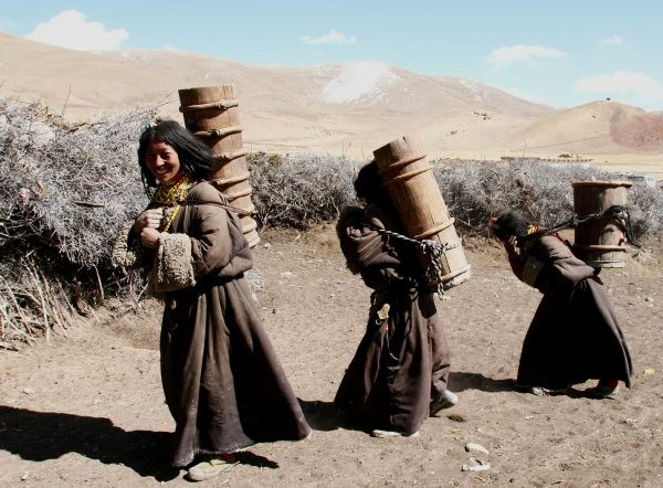 Kangba women carry barrels to fetch water at a village on April 10, 2005 in Zuogong County of Tibet, China. (China Photos/Getty Images)